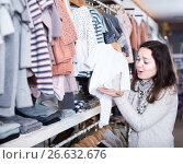 Купить «Young female choosing romper suit for baby in store», фото № 26632676, снято 10 января 2017 г. (c) Яков Филимонов / Фотобанк Лори