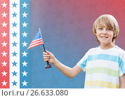 Купить «Smiling boy holding an american flag for independence day», фото № 26633080, снято 26 июня 2019 г. (c) Wavebreak Media / Фотобанк Лори