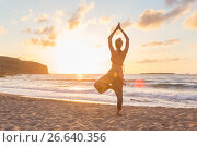 Купить «Woman practicing yoga on sea beach at sunset», фото № 26640356, снято 27 февраля 2020 г. (c) Matej Kastelic / Фотобанк Лори