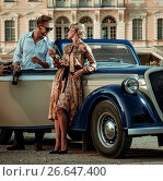 Wealthy couple near classic convertible against royal palace. Стоковое фото, фотограф Andrejs Pidjass / Фотобанк Лори