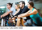 Active adults riding stationary bicycles, фото № 26649940, снято 22 июля 2017 г. (c) Яков Филимонов / Фотобанк Лори