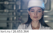 Купить «Young engineer woman at hard hat», видеоролик № 26653364, снято 10 июля 2017 г. (c) Илья Шаматура / Фотобанк Лори
