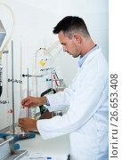 Купить «Adult man working on quality of products in lab», фото № 26653408, снято 12 декабря 2019 г. (c) Яков Филимонов / Фотобанк Лори