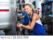 Купить «Mechanic woman working on wheel equilibrium control machinery», фото № 26653596, снято 17 июля 2018 г. (c) Яков Филимонов / Фотобанк Лори