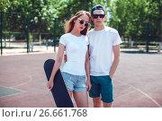 Купить «Young skater boy and girl with skateboard in white T-shirts on the basketball court.», фото № 26661768, снято 30 июня 2017 г. (c) Женя Канашкин / Фотобанк Лори