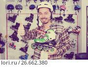 Купить «Male customer examining roller-skates», фото № 26662380, снято 21 декабря 2016 г. (c) Яков Филимонов / Фотобанк Лори
