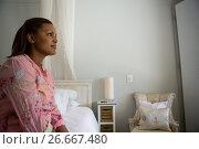 Купить «Woman sitting on bed in the bedroom at home», фото № 26667480, снято 24 марта 2017 г. (c) Wavebreak Media / Фотобанк Лори
