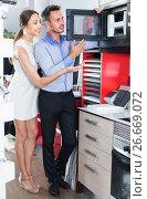 Купить «Man and woman are choosing new microwave», фото № 26669072, снято 15 июня 2017 г. (c) Яков Филимонов / Фотобанк Лори