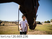 Smiling girl holding the rein of the horse in the ranch. Стоковое фото, агентство Wavebreak Media / Фотобанк Лори