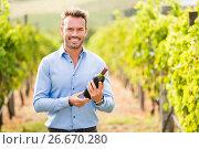 Купить «Portrait of man holding wine bottle», фото № 26670280, снято 16 февраля 2016 г. (c) Wavebreak Media / Фотобанк Лори