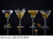 Купить «Olives splashing in to a cocktail martini with lime on table», фото № 26673064, снято 15 февраля 2017 г. (c) Wavebreak Media / Фотобанк Лори