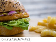 Купить «Close up of hamburger by french fries», фото № 26674492, снято 13 января 2017 г. (c) Wavebreak Media / Фотобанк Лори