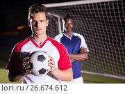 Купить «Portrait of confident soccer player holding ball with rival athlete», фото № 26674612, снято 25 января 2017 г. (c) Wavebreak Media / Фотобанк Лори