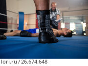 Купить «Low section of male boxer standing against referee by athlete», фото № 26674648, снято 22 января 2017 г. (c) Wavebreak Media / Фотобанк Лори