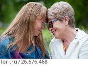 Купить «Пожилая мама и взрослая дочка сидят прислонившись лбами друг к другу», фото № 26676468, снято 8 июня 2017 г. (c) Кекяляйнен Андрей / Фотобанк Лори