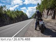 Купить «Вид сзади на мотоциклиста, сидящего на мотоцикле на обочине горной дороги», фото № 26676488, снято 14 июля 2017 г. (c) Кекяляйнен Андрей / Фотобанк Лори