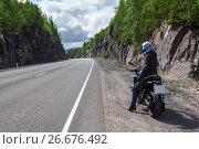 Купить «Мотоциклист с мотоциклом стоит на обочине пустой горной дороги», фото № 26676492, снято 14 июля 2017 г. (c) Кекяляйнен Андрей / Фотобанк Лори