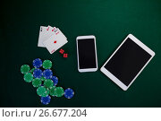 Купить «Electronic gadgets, playing cards, mobile phone, dice and casino chips on poker table», фото № 26677204, снято 6 апреля 2017 г. (c) Wavebreak Media / Фотобанк Лори