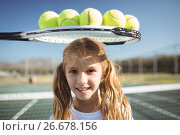 Купить «Smiling girl standing below tennis racket and balls», фото № 26678156, снято 11 марта 2017 г. (c) Wavebreak Media / Фотобанк Лори