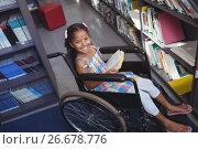 Купить «Portrait of smiling girl with book on wheelchair», фото № 26678776, снято 11 марта 2017 г. (c) Wavebreak Media / Фотобанк Лори