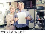 Купить «Nice mature couple buying on credit agreement for home appliances», фото № 26691564, снято 5 апреля 2020 г. (c) Яков Филимонов / Фотобанк Лори