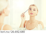 Купить «woman brushing eyebrow with brush at bathroom», фото № 26692680, снято 13 февраля 2016 г. (c) Syda Productions / Фотобанк Лори