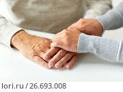 Купить «close up of old man and young woman holding hands», фото № 26693008, снято 7 июля 2016 г. (c) Syda Productions / Фотобанк Лори