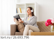 Купить «happy woman with tablet pc and headphones at home», фото № 26693796, снято 22 апреля 2017 г. (c) Syda Productions / Фотобанк Лори