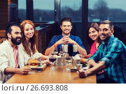 friends taking selfie by smartphone at restaurant. Стоковое фото, фотограф Syda Productions / Фотобанк Лори