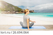 Купить «woman doing yoga in twist pose on beach», фото № 26694064, снято 13 ноября 2015 г. (c) Syda Productions / Фотобанк Лори