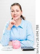 Купить «Portrait of a successful young woman with a piggy bank and money at the table», фото № 26694788, снято 26 февраля 2017 г. (c) Константин Лабунский / Фотобанк Лори