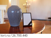 Купить «photo frame with mourning ribbon and cremation urn», фото № 26700440, снято 20 марта 2017 г. (c) Syda Productions / Фотобанк Лори