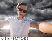 Купить «man taking casual selfie photo in front of dramatic dark cloud landscape», фото № 26710488, снято 5 июля 2020 г. (c) Wavebreak Media / Фотобанк Лори