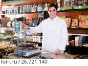 Купить «Woman seller weighing on scales festive chocolate cake», фото № 26721140, снято 24 января 2017 г. (c) Яков Филимонов / Фотобанк Лори