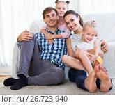 Купить «Relaxed family of four posing», фото № 26723940, снято 18 октября 2018 г. (c) Яков Филимонов / Фотобанк Лори