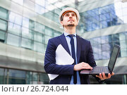 Купить «Man with documents in suit and helmet working at the laptop», фото № 26724044, снято 29 апреля 2017 г. (c) Яков Филимонов / Фотобанк Лори