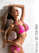 Купить «Gorgeous girl in fine pink bicini posing on sunny wall», фото № 26724960, снято 24 июля 2017 г. (c) Гурьянов Андрей / Фотобанк Лори
