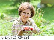 Купить «Portrait of a smiling female with a bowl of freshly picked strawberry», фото № 26726824, снято 29 июля 2017 г. (c) Юлия Кузнецова / Фотобанк Лори