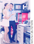 Купить «Smiling husband and wife are choosing new microwave», фото № 26727616, снято 15 июня 2017 г. (c) Яков Филимонов / Фотобанк Лори