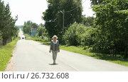 Elderly woman walking on the road in the village. Стоковое видео, видеограф worker / Фотобанк Лори