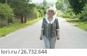 Купить «Old woman walking on the road at the sunny day», видеоролик № 26732644, снято 25 июля 2017 г. (c) worker / Фотобанк Лори