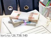 Купить «Время платить налоги. Пачки денег на деловой папке», фото № 26738140, снято 3 августа 2017 г. (c) Наталья Осипова / Фотобанк Лори
