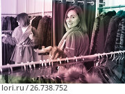 Купить «Woman trying on sheepskin coat in women's cloths store», фото № 26738752, снято 27 января 2020 г. (c) Яков Филимонов / Фотобанк Лори