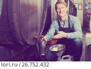 man working in winery pouring wine from wood to plastic bottle in cellar. Стоковое фото, фотограф Яков Филимонов / Фотобанк Лори