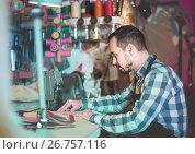 Купить «male worker sewing stitches on belt in leather workshop», фото № 26757116, снято 22 марта 2019 г. (c) Яков Филимонов / Фотобанк Лори