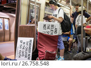 Купить «An Asian Evangelical church member travels on the subway in New York with her signs», фото № 26758548, снято 18 июня 2017 г. (c) age Fotostock / Фотобанк Лори