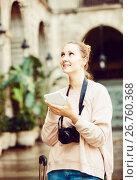 Купить «blond young girl holding tablet in hands and looking up her way using app, gps», фото № 26760368, снято 4 мая 2017 г. (c) Яков Филимонов / Фотобанк Лори