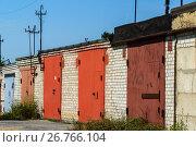 Купить «Brick garages with red metal gates of garage cooperative», фото № 26766104, снято 14 августа 2017 г. (c) Володина Ольга / Фотобанк Лори