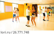 Купить «Smiling adults dancing bachata together in dance studio», видеоролик № 26771748, снято 6 июля 2017 г. (c) Яков Филимонов / Фотобанк Лори