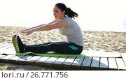 Купить «Young smiling woman training on beach by sea in sunny morning», видеоролик № 26771756, снято 17 апреля 2017 г. (c) Яков Филимонов / Фотобанк Лори